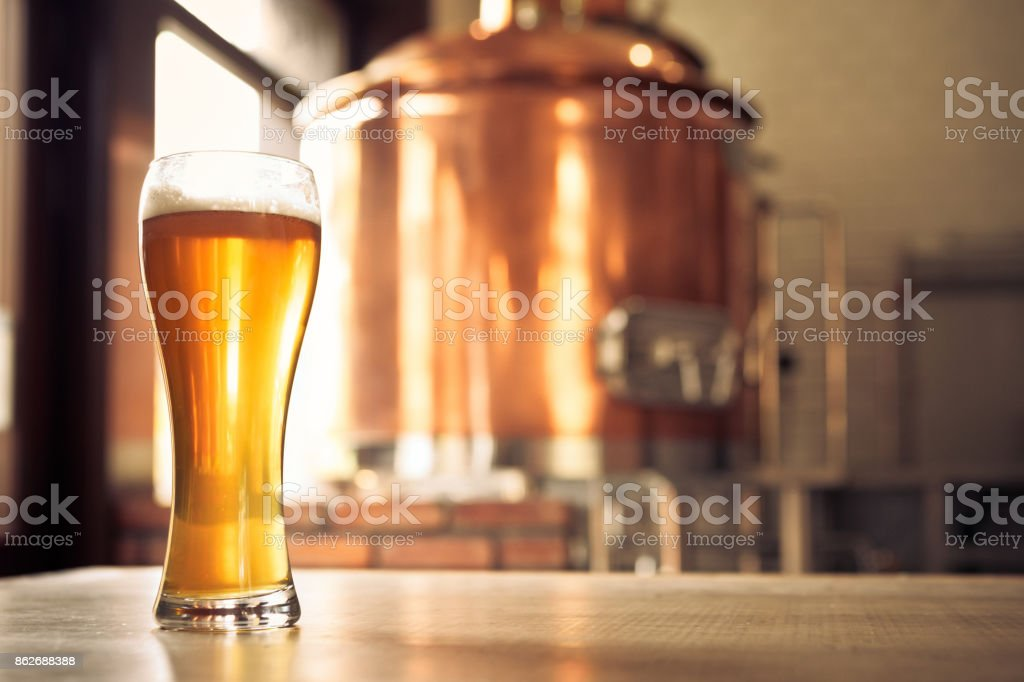 Glass of lager beer in front of copper vat stock photo