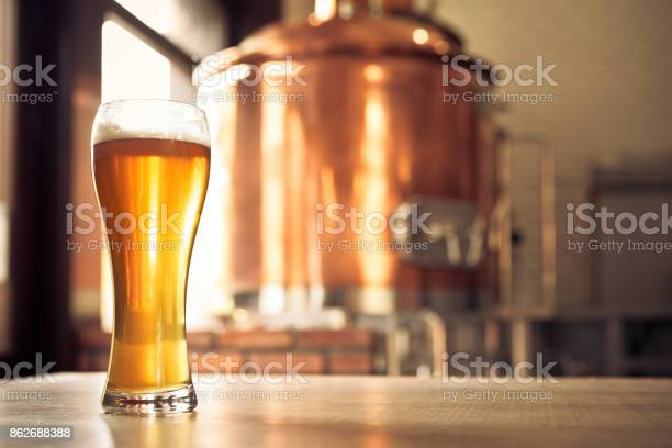 Glass Of Lager Beer In Front Of Copper Vat Stock Photo - Download Image Now