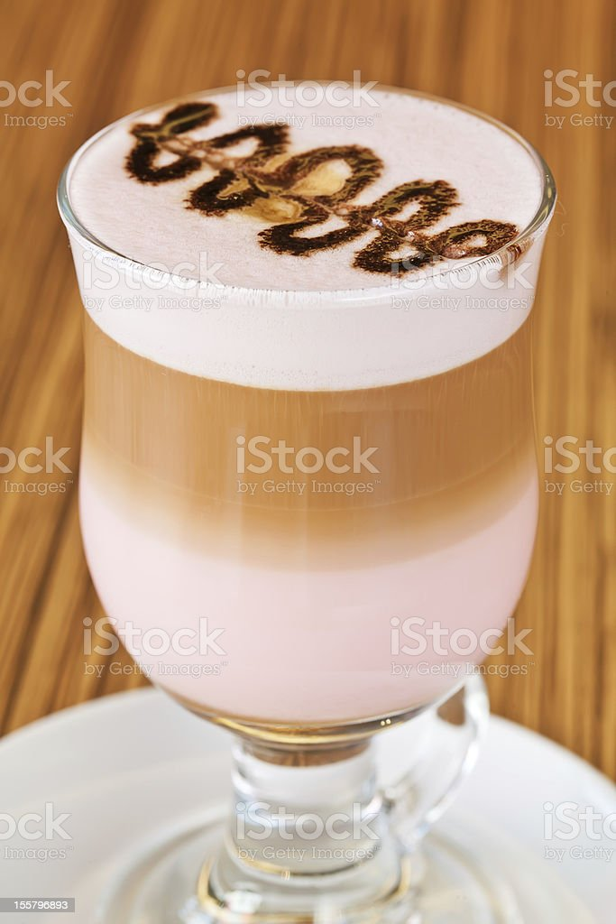 Glass of latte macchiato coffee with grenadine syrup, arranged in royalty-free stock photo