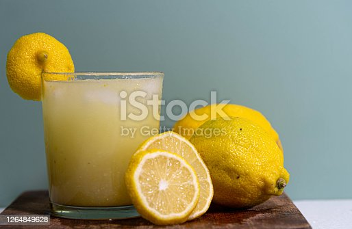 Glass of lemon juice and fruits. A Sicilian Lemon contains 88% of vitamin C. In addition, it is rich in vitamin A, vitamin B1, vitamin B2 and vitamin B3, iron, phosphorus, magnesium and potassium.