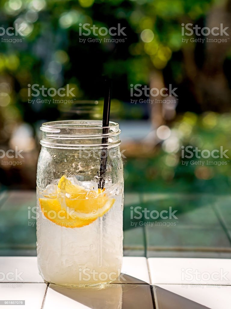 A glass of Lemon soda water mojito with lemonade or lemon juice with beautiful sunlight and shadow for summer or beach juice drinking idea stock photo