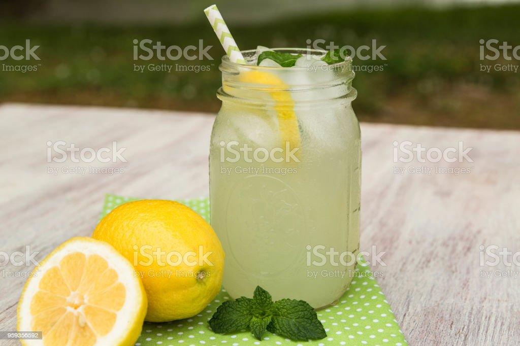 Glass of Lemonade and Lemons Outside In Summer stock photo