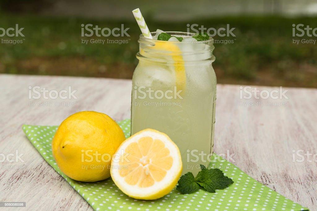 Glass of Lemonade On Green Napkin Outside In Summer stock photo