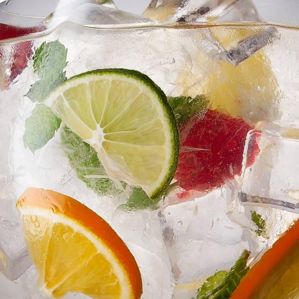 Vaso de limonada con limón, lima y menta sobre fondo blanco.  Agua gaseosa con cítricos y hielo. Lima y naranja en agua con gas - foto de stock