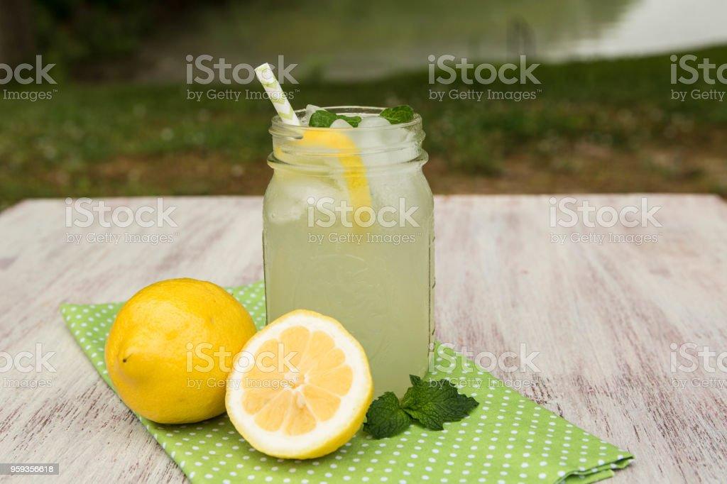 Glass of Lemonade with Lemons Outside By Lake stock photo