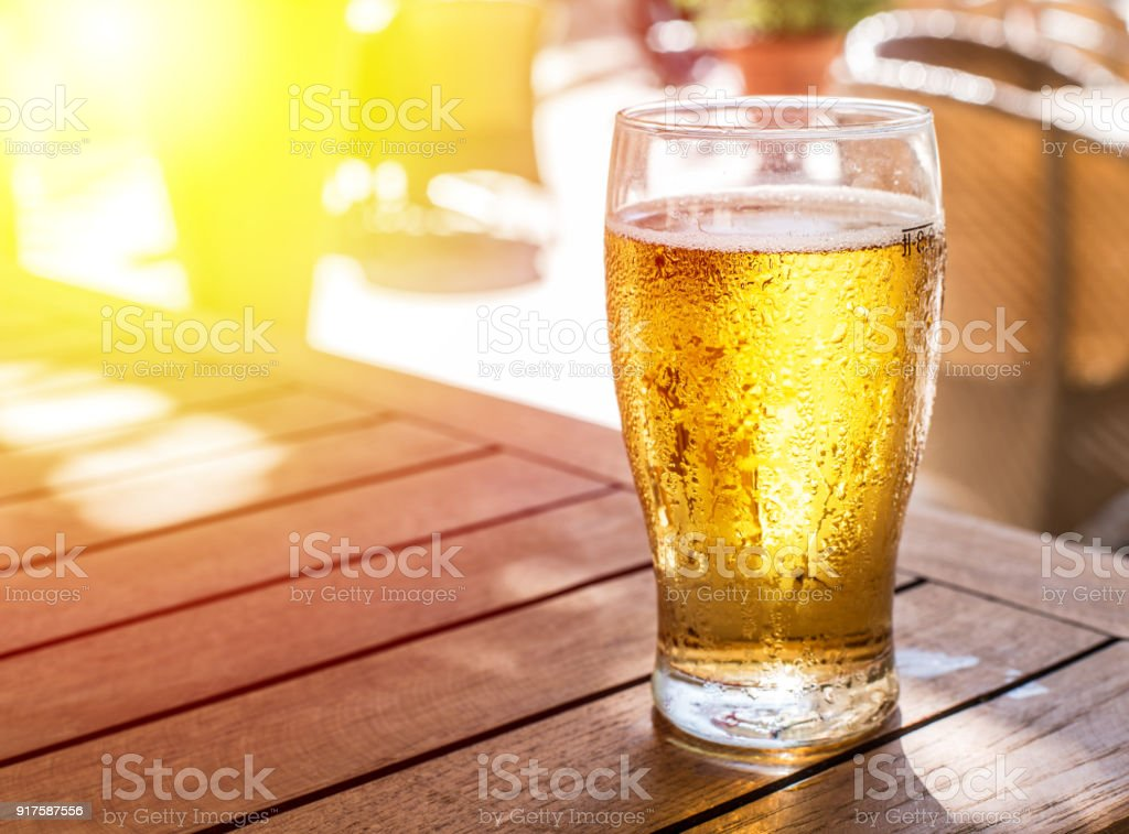 Glass of light beer on the wooden table. stock photo