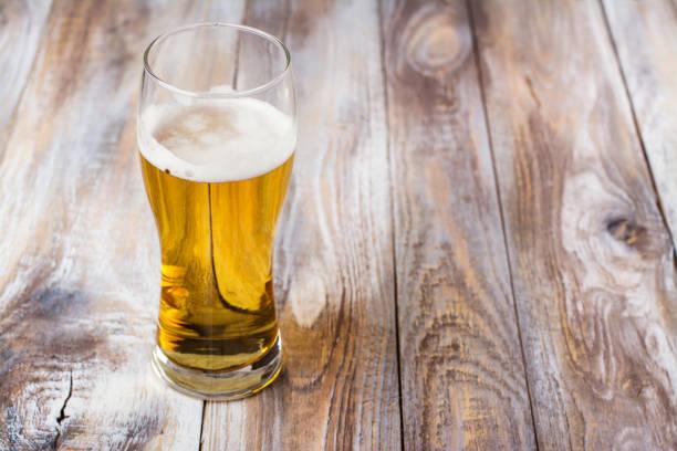 Glas helles Bier auf Holzhintergrund – Foto