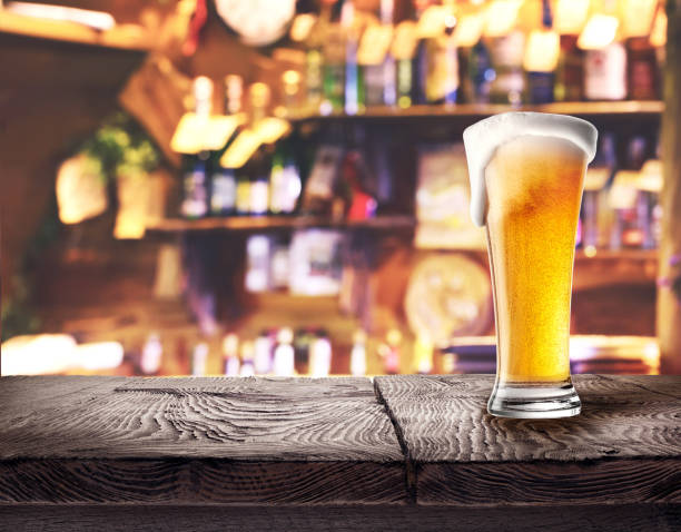 Glass of light beer on wooden board stock photo