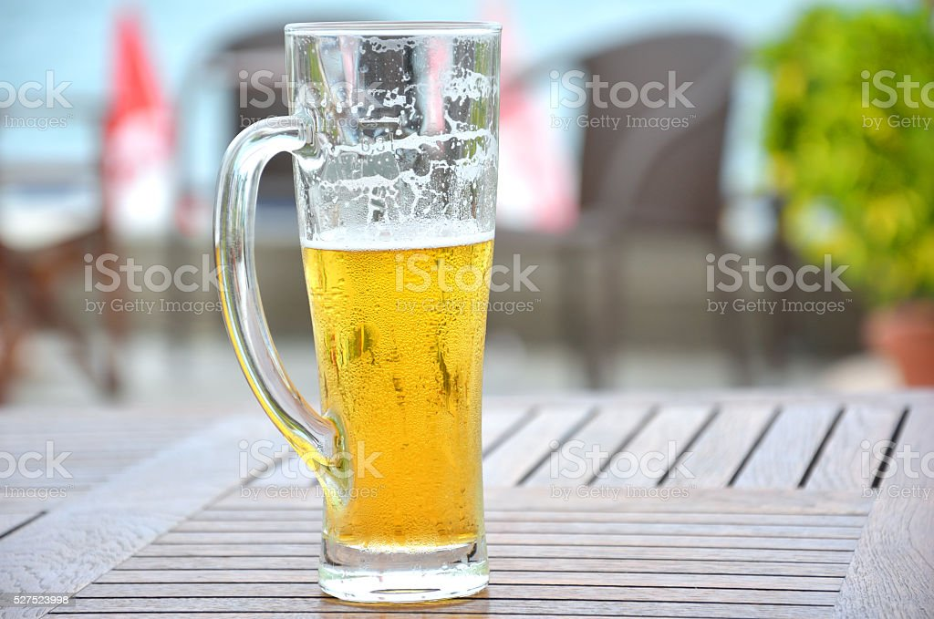 Glass of Light Beer on Wooden Table stock photo