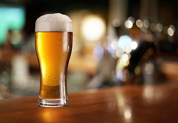 Glass of light beer. Glass of light beer on a dark pub. beer glass stock pictures, royalty-free photos & images