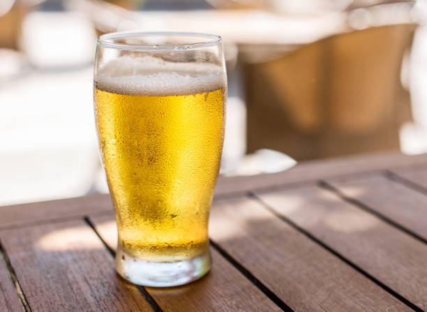 Glass of light beer. Glass of light beer on the wooden table. lager stock pictures, royalty-free photos & images
