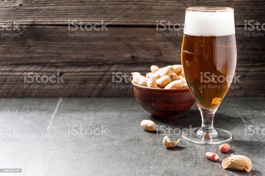 Glas kalten Milchschaum Leichtbier, Muttern auf einem alten hölzernen Hintergrund – Foto