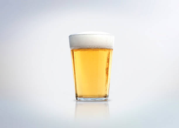 Glass of light lager beer with foam. stock photo