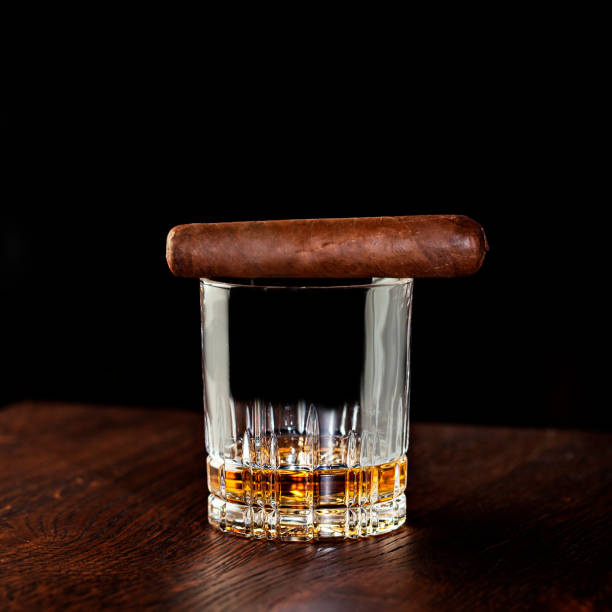 glass of liquor with smoking cigar on wooden table - tamara dragovic stock photos and pictures