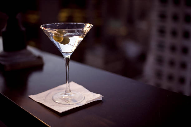 Glass of martini on a white napkin sipping a martini in mid Manhattan martini stock pictures, royalty-free photos & images