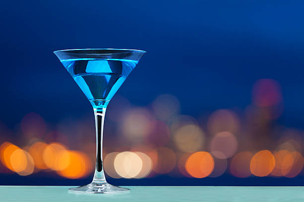 Glass of martini standing against city lights stock photo
