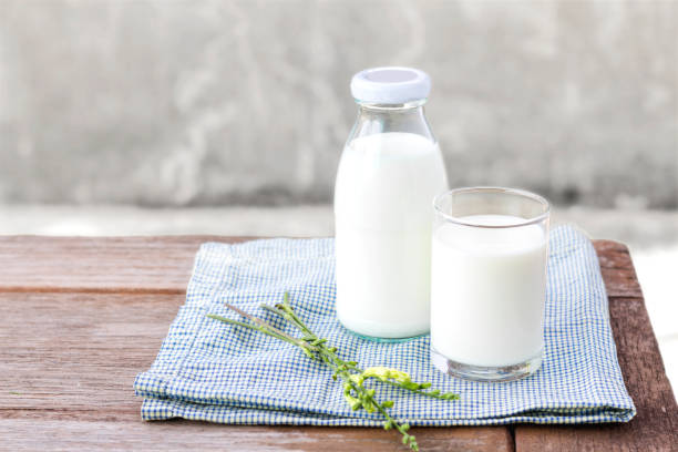 glass of milk and bottle of milk on the wood table. stock photo