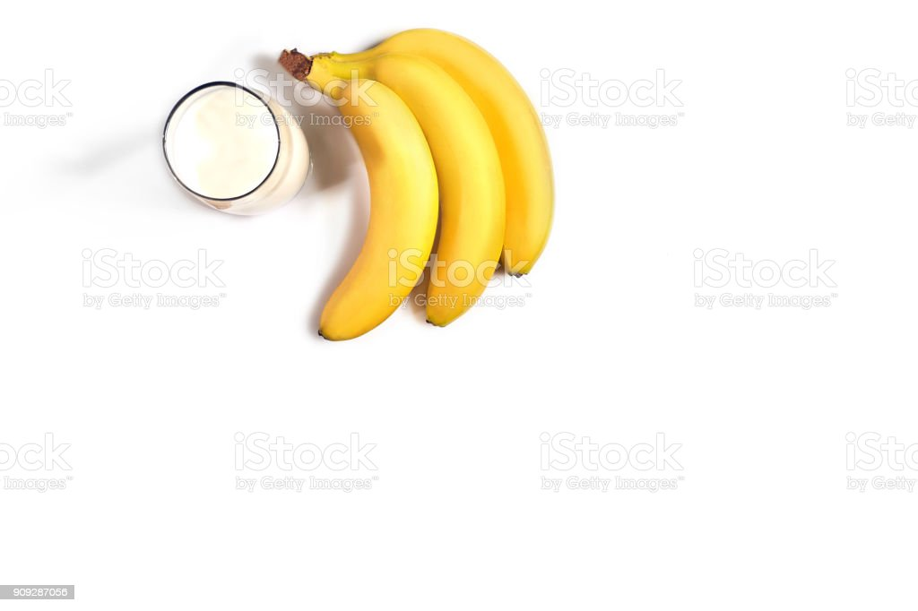 Glass of milk with bananas over white background. Top view stock photo