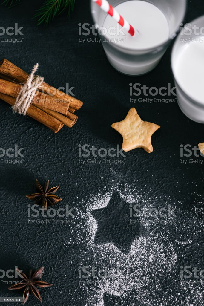 Glass of milk with star shaped cookies, spices and sugar powder on black, top view royalty-free stock photo
