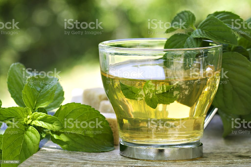 A glass of mint tea on a table covered in mint leaves stock photo