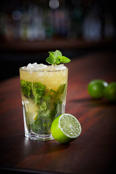 Glass of mojito with half a lime on a wooden table Mojito On The Bar Counter mojito stock pictures, royalty-free photos & images