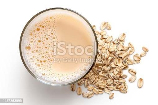 Glass of oat drink  next to a pile of dry oats isolated on white from above.