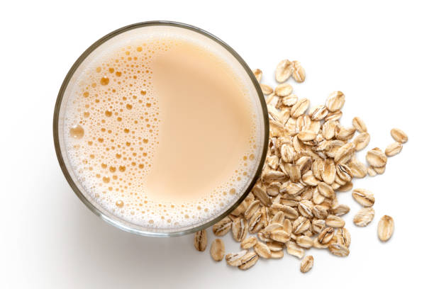 glass of oat drink  next to a pile of dry oats isolated on white from above. - fotos de oats imagens e fotografias de stock