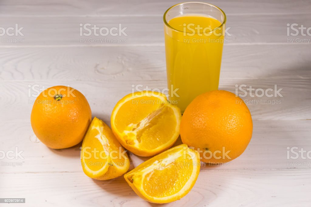 Glass of orange juice and fresh oranges on white wooden table