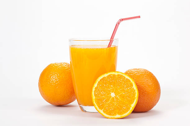 Glass of orange juice and three oranges over white backdrop stock photo