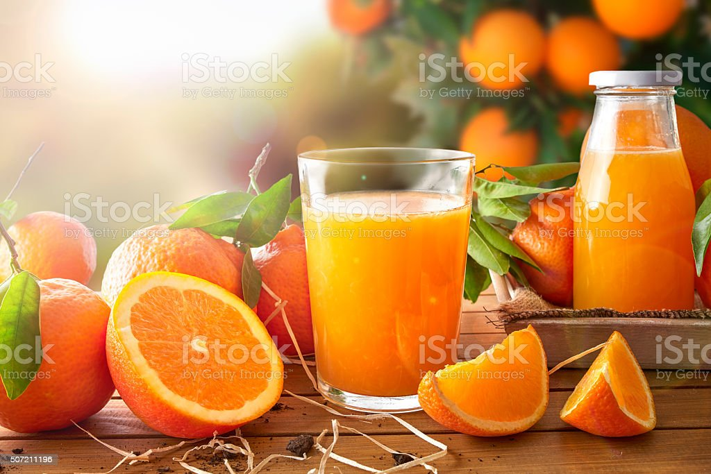 Glass of orange juice on a wooden in field stock photo