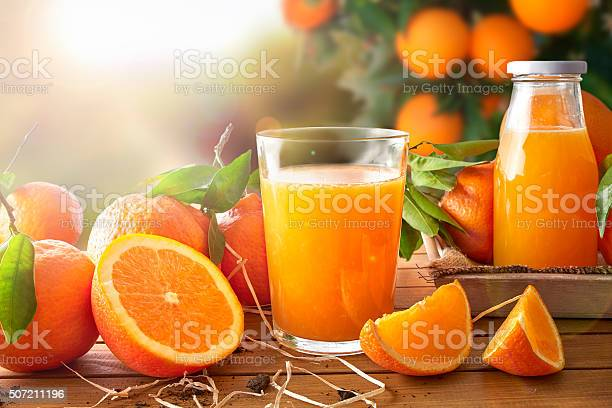 Glass of orange juice on a wooden table with bottle and orange sections. Tree and field background with evening sun. Horizontal composition. Front view
