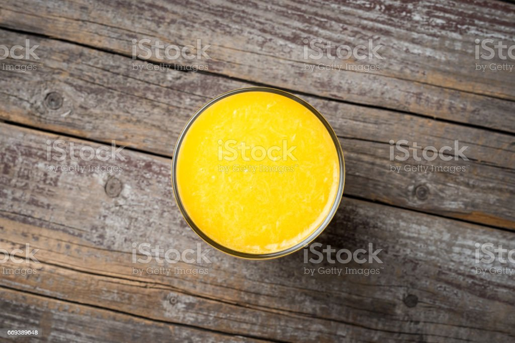 Glass of orange juice on an old wooden background stock photo