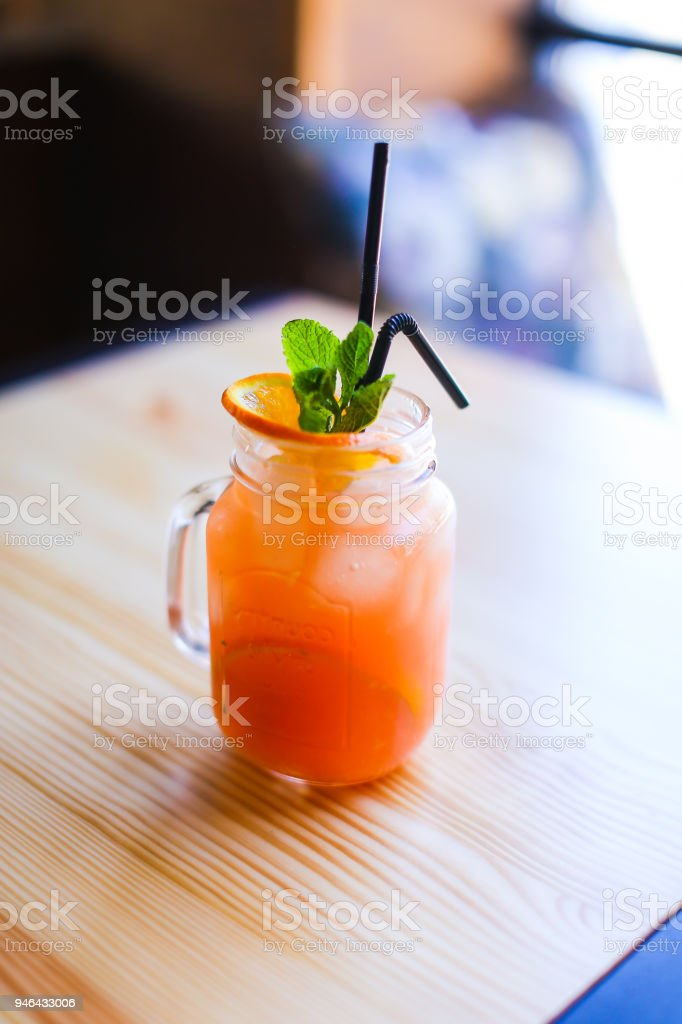 Glass of orange juice on wooden table in luncheonette stock photo