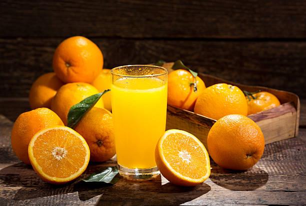 glass of orange juice with fresh fruits stock photo