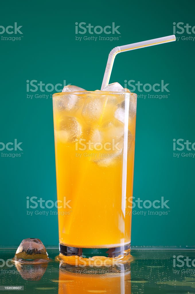 Glass of orange soda with ice and striped yellow straw stock photo