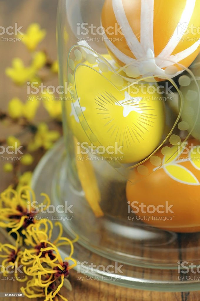 Glass of ornate Easter egg with Witchhazle and Forsythia stock photo