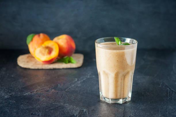 glas pfirsich frucht-smoothie mit minze und zutaten auf dem dunklen hintergrund. gesunde, vegetarische, vegane ernährung lebensmittel. tiefenschärfe, platz für text. - pfirsich milchshake stock-fotos und bilder