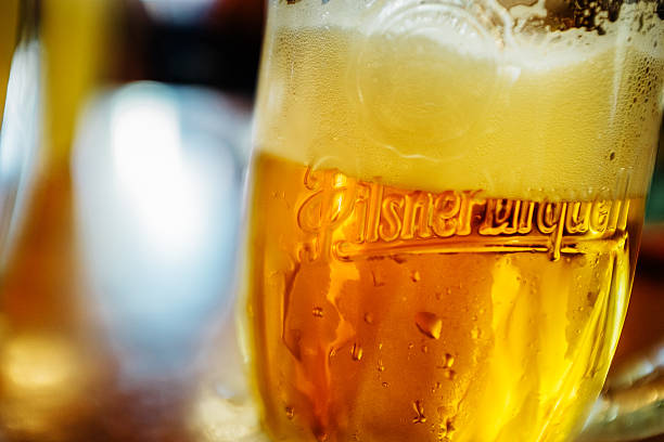 Glass of Pilsner Urquell Beer Pilsen, Czech Republic - July 22, 2015: Glass of Pilsner Urquell Beer with condensed water and logo on glass. Pilsner Urquell, the first pilsner beer in the world, known better by its German name Pilsner Urquell is a prominent brand of the global brewing company SABMiller. pilsner stock pictures, royalty-free photos & images