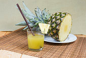 Pineapple juice in glass with drinking straw and fresh pineapple slice on a background of upper part of fresh pineapple with tuft of stiff leaves on a bamboo table mat