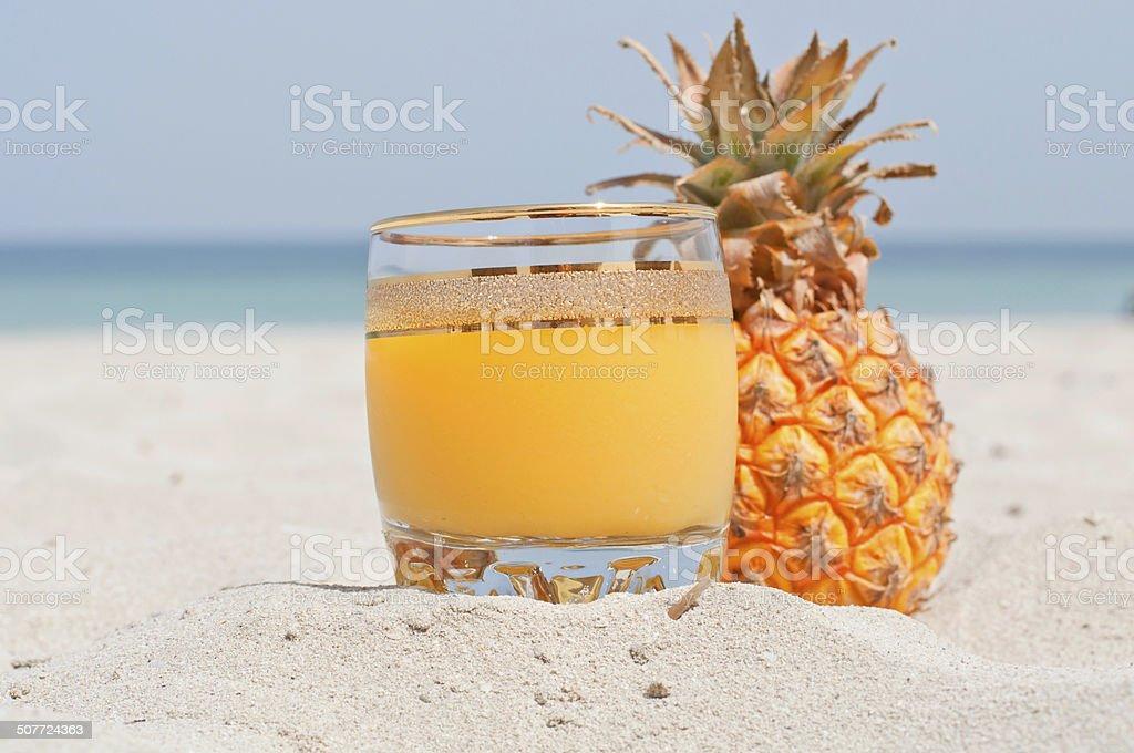 Glass of pineapple juice on a beach stock photo