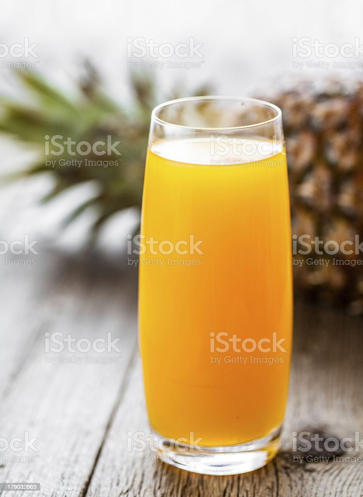 Glass of pineapple juice on wooden table. royalty-free stock photo