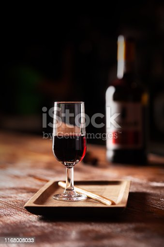 Glass of port wine on wooden table and over dark background, vertical orientation. Aperitif