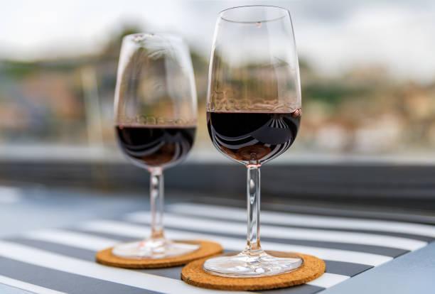 glass of port wine with the blurred cityscape of porto portugal in the background - esplanada portugal imagens e fotografias de stock