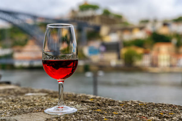 Glass of port wine with the blurred cityscape of Porto Portugal in the background stock photo