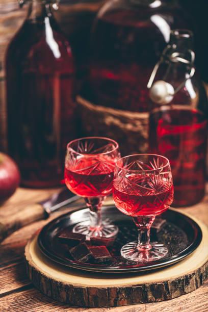 glas roter schnaps mit schokoriegeln - holunderlikör stock-fotos und bilder