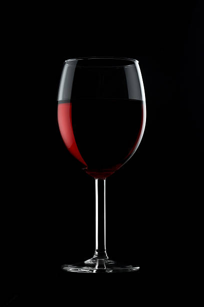 Glass of red wine against black background stock photo