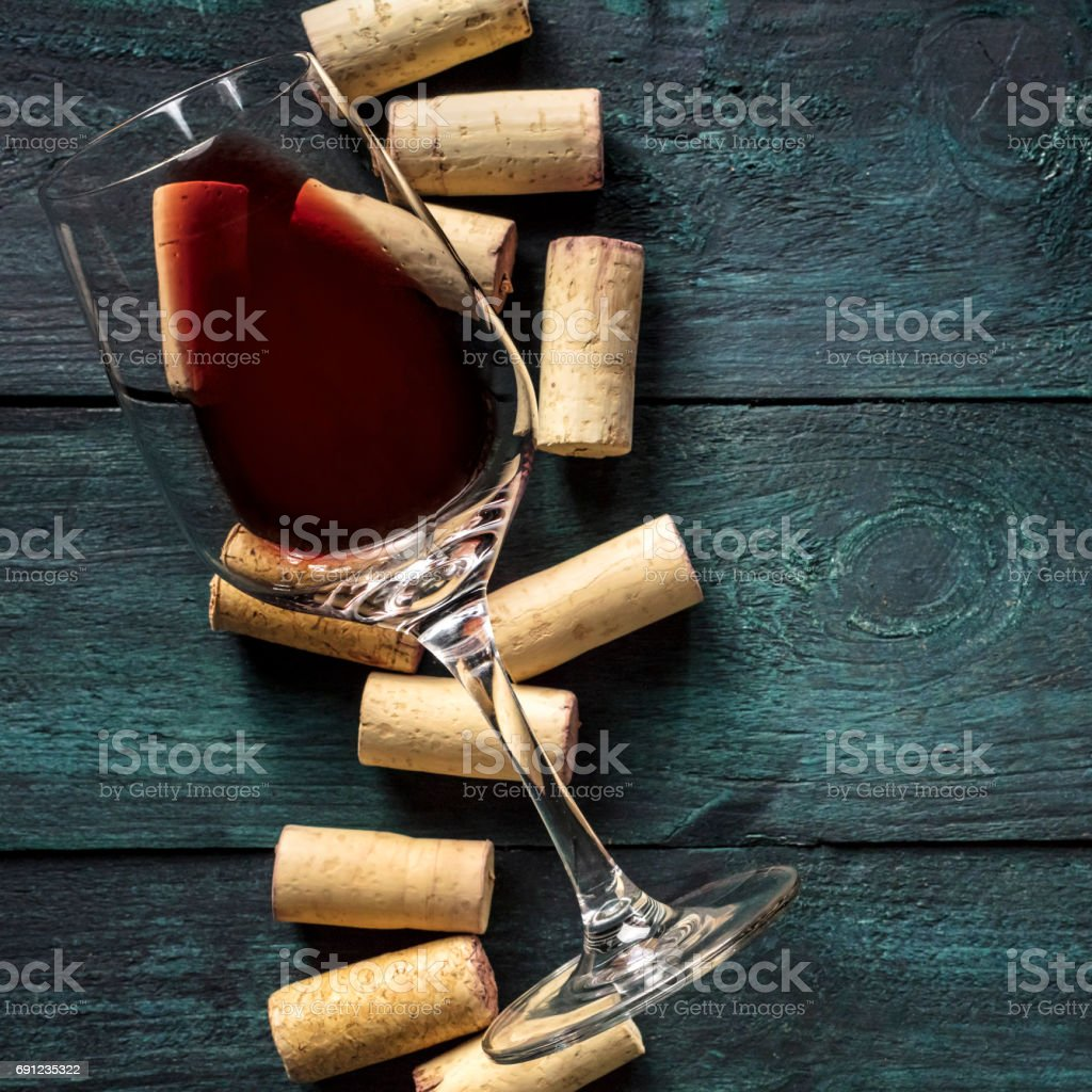 Glass of red wine and corks on dark background stock photo