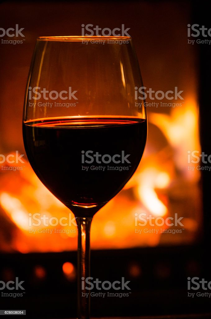Glass of red wine and fireplace stock photo