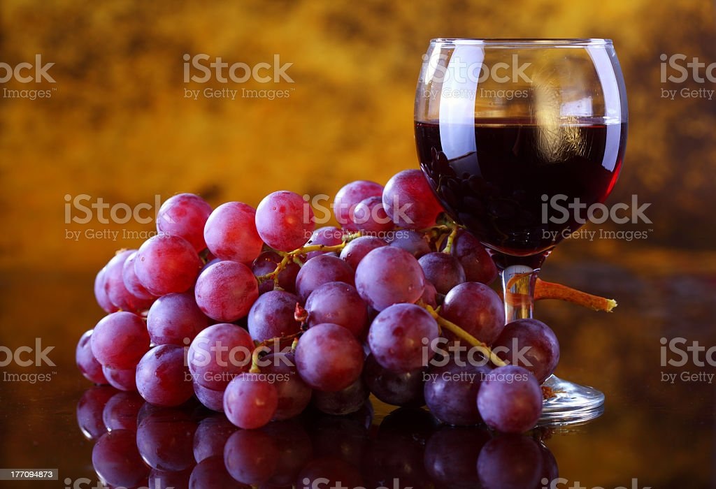 A glass of red wine and red grapes stock photo