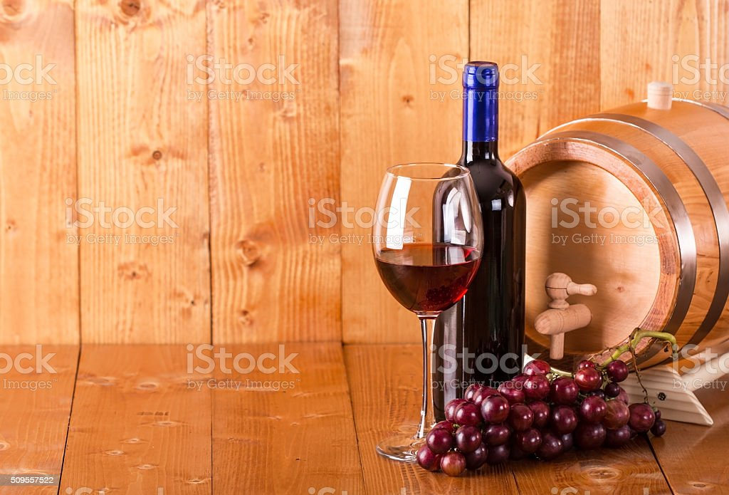 Glass of red wine bottle barrel and grapes stock photo